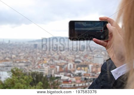 Woman records a video overlooking a large city