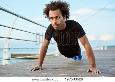 Motivated and concentrated Afro-American athlete with bushy hair wearing black running outfit standing in plank position on a wooden platform. Dark-skinned male runner preparing for morning workout session.