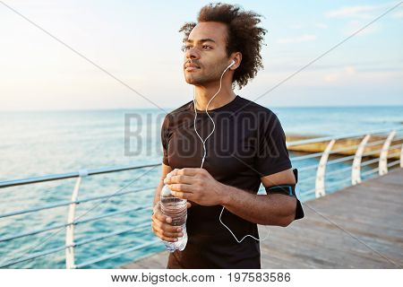 Portrait of mediative and concentrated dark-skinned male athlete with bushy hair holding bottle of mineral water in his hands. Sportsman in black sportswear wearing white earphones enjoying morning workout session by the sea.
