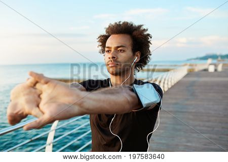 Afro-American male runner with beautiful athletic body and bushy hair stretching muscles, raising his arms while warming up before morning workout session. Young man athlete exercising outdoors.