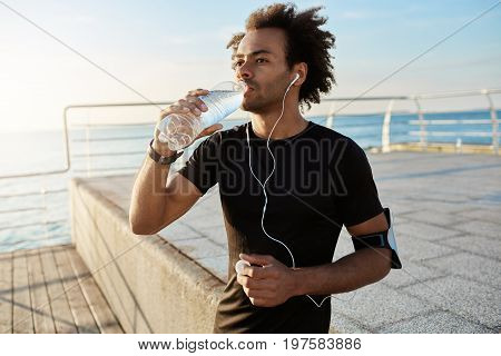 Fit afro-american male athlete drinking water out of plastic bottle after jogging on the pear in the morning. Shot of male runner in black top wearing white earphones listening to a favourite songs while doing exercises outdoors. Enjoying music and sport.