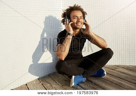 Joyful smiling Afro American man with bushy hairstyle wearing big headphones. Handsome muscular dark-skinned guy enjoying music, sitting cross-legged on wooden platform on a white background wearing black sport suite and earphones.