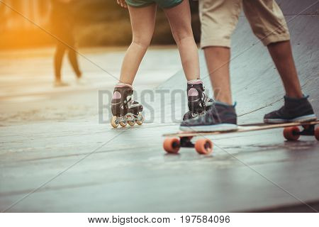 Skateboarder on a grind with dark clouds background at the local skate park at sunset