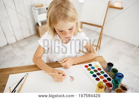 Indoor shot of busy and concentrated on aquarelle painting cute little blonde. Girl with fair hair wearing white T-shirt sitting at the desk holding brush in hand and drawing in the filled with light art room.