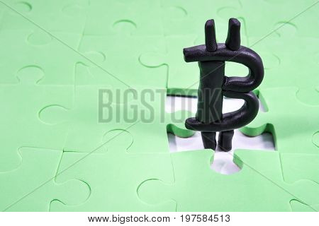 Plasticine bitcoin sign in the hole of the folded puzzle