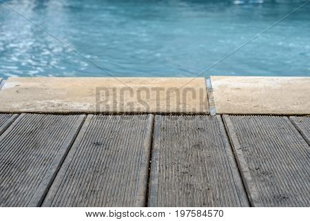Swimming pool and wooden deck and bricks for the background