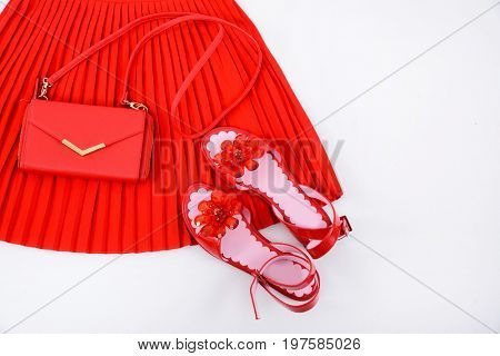Red pleated skirt with floral red shoes with handbag isolated