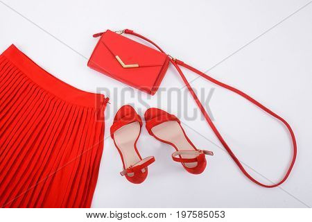 Red pleated skirt with red shoes and handbag isolated