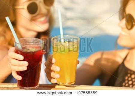 Beautiful young women clinking glasses with cocktails while relaxing in pool, closeup