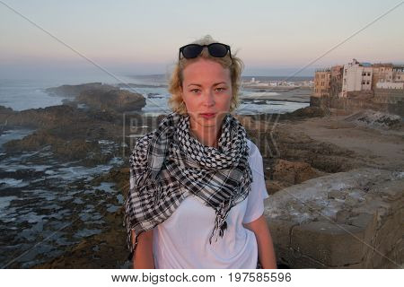 Female traveler standing on city fortress wall of Essaouira, Morocco in sunset. Travel lifestyle adventure concept. Active vacations. Solo female world traveler. Strong indepandant woman.