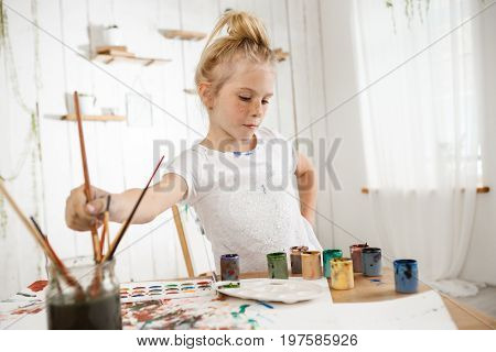 Focused on creative process cute little blond with hair bun and freckled face in white t-shirt in art room. Creative and talented female child busy with drawing, deeping brush into water, thinking about her picture.