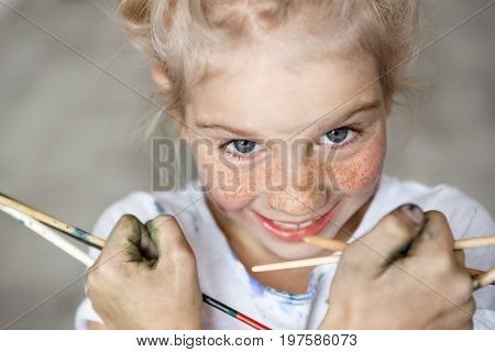 Close up portrait of adorable blonde little female child in white t-shirt holding brushes, having fun, enjoying drawing with happy expression, against concrete background. Selective focus.