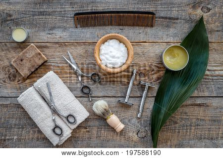 Barber workplace. Shaving brush, razor, foam on wooden table background top view.