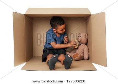 Cute little boy living in box on white background. Poverty concept