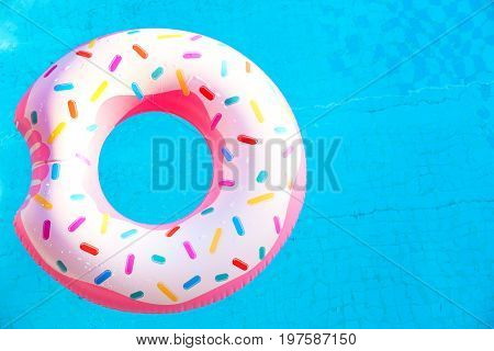 Inflatable rubber ring in shape of donut in pool