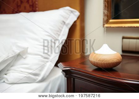 Aroma oil diffuser on table near bed