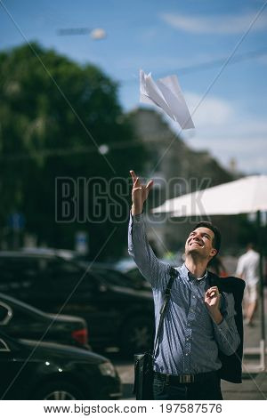 Happy young man took vacation. Joyful and free businessman on street