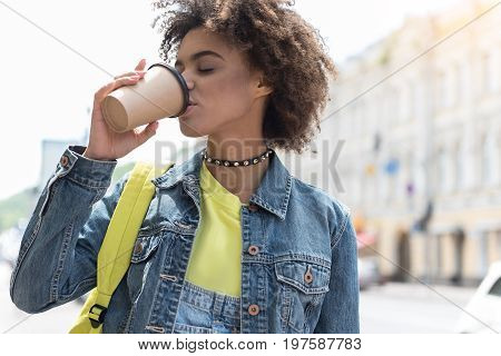 Favorite beverage. Charming young mulatto woman is drinking hot aromatic espresso with pleasure while spending time in city