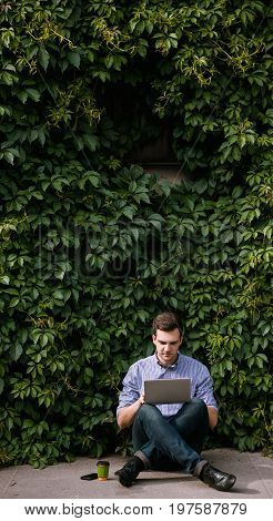 Freelancer introvert working on the street. Creative open-minded man, modern technology. Nature concept