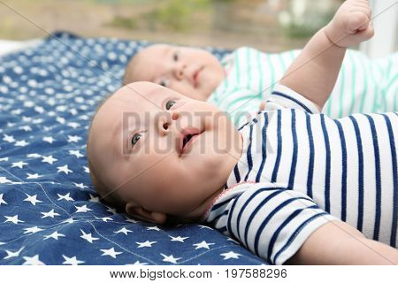 Beautiful baby twins lying together on bed