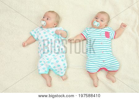 Beautiful baby twins lying with pacifiers on plaid