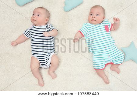 Beautiful baby twins lying together on plaid