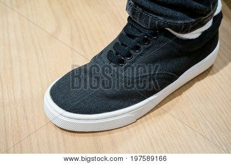 Black Canvas Sneaker Under Dark Boot Cut Jeans