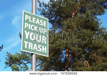 Signboard with text PLEASE PICK UP YOUR TRASH at park