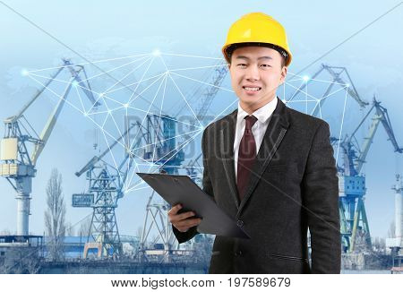 Manager with clipboard and dock cranes on background. Wholesale and logistic concept