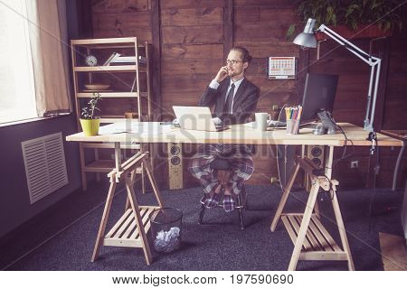 Freelancer working remotely on project. Modern concept of freelance work. Man wering jacket and home pants at home office, Toned image.
