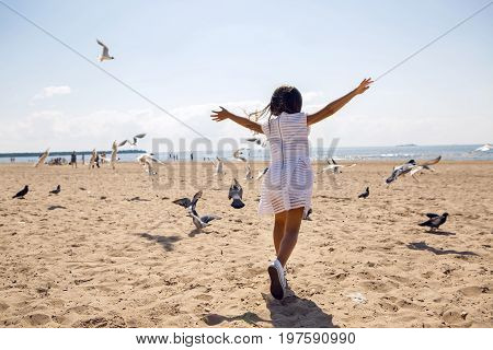 girl runs on the beach dispersing birds seagulls and they fly