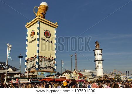 Munich, Germany - September 24, 2016: Roof of the Paulaner tower with the famous beer stein and the Loewnbraeu tower with the lion sculpture unidentified people are walking by