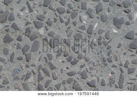 Old road paved with stones or cobbles. The stones are smoothed chamfered rolled. Road with cracks. Stones of different sizes large and small.