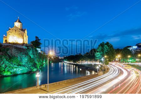 Metekhi church and traffic and blurry lights of cars on multi-lane highways and road junction at night in Tbilisi, Georgia