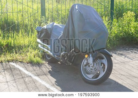 The Parking lot is a motorcycle covered with a canvas wrap. Parking paved with white markings. Behind the fence and the green grass grows. Visible exhaust pipes and the front wheel.