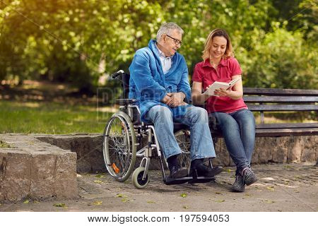 Spending time together reading book outdoor cheerful daughter and disabled father in wheelchair