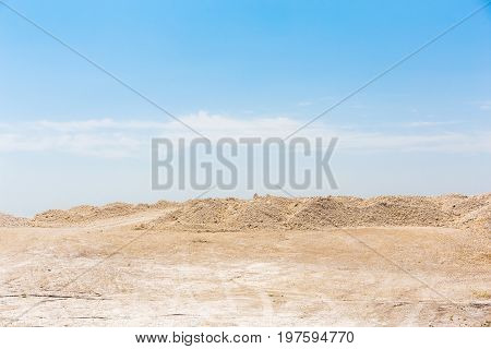 Chalk or Cretaceous quarry, sand or chalk hills against a bright blue sky. Desert sands