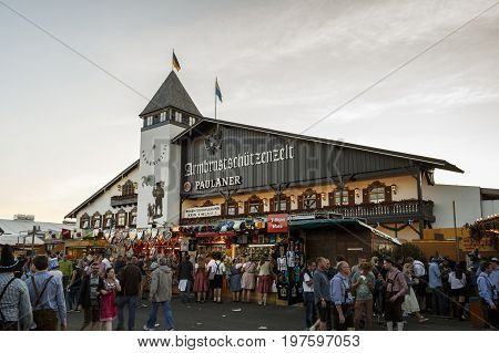 Munich, Germany - September 24, 2016: Facade of the Armbrustschuetzenzelt with the balcony and beautiful paintings and people standing on the main street