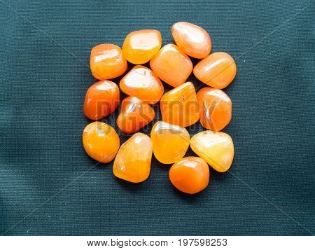 Tumbled Carnelian Stones On Black Cloth For Crystal Therapy Treatments And Reiki