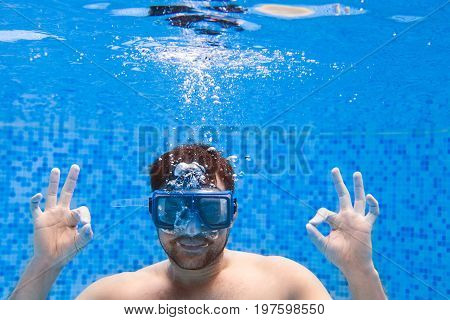 Young Man In Diving Mask Swimming The Front Crawl In A Pool, Taken Under Water