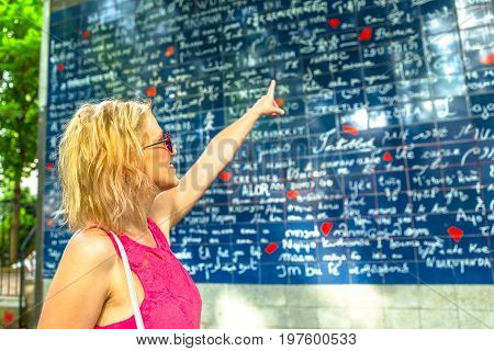 Blonde elegant woman pointing popular Mur des Je t'aime. I Love You Wall is a monument landmark in Jehan Rictus garden square near Place des Abesses, Montmartre, Paris, France. Love and couple concept