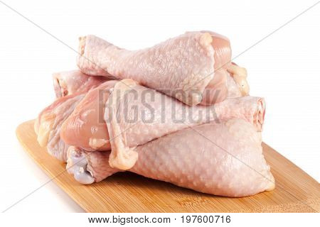 raw chicken drumsticks on a wooden cutting boardn white background.