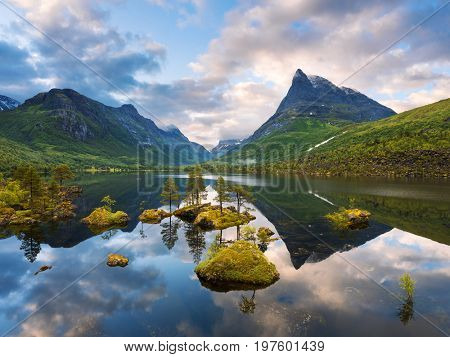 Innerdalen - mountain valley of Norway. Summer landscape with Innerdalsvatna Lake and the mountain peak of Innerdalstarnet. Reflection in mirror water. Beautiful view at dawn