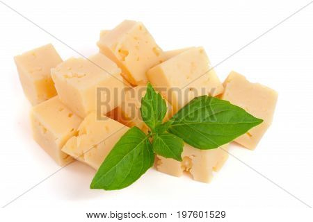 cheese cut into cubes with basil leaves isolated on white background.