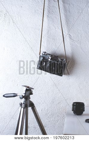 Old Camera And Tripod On A White Concrete Background