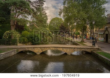 Bourton-on-the-water, 2017-07-24. Bourton-on-the-Water is a village and civil parish in Gloucestershire, England that lies on a wide flat vale within the Cotswolds Area of Outstanding Natural Beauty.