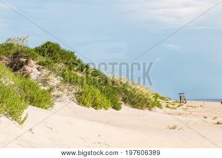 Sand dune covered in beach grass and empty lifeguard chair at Coquina Beach, Cape Hatteras National Seashore.