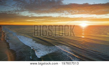 Aerial view over the ocean of sun rising through a colourful cloudy sky, on Gold Coast beach.