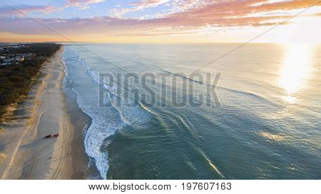 Aerial view of ocean and beach with a colorful cloudy sky, on Gold Coast beach.