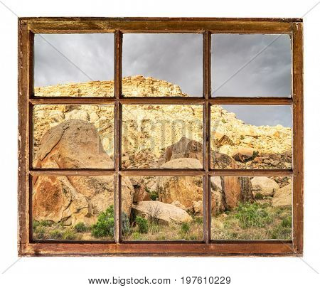 desert rocks and cliffs as seen  through vintage, grunge, sash window with dirty glass